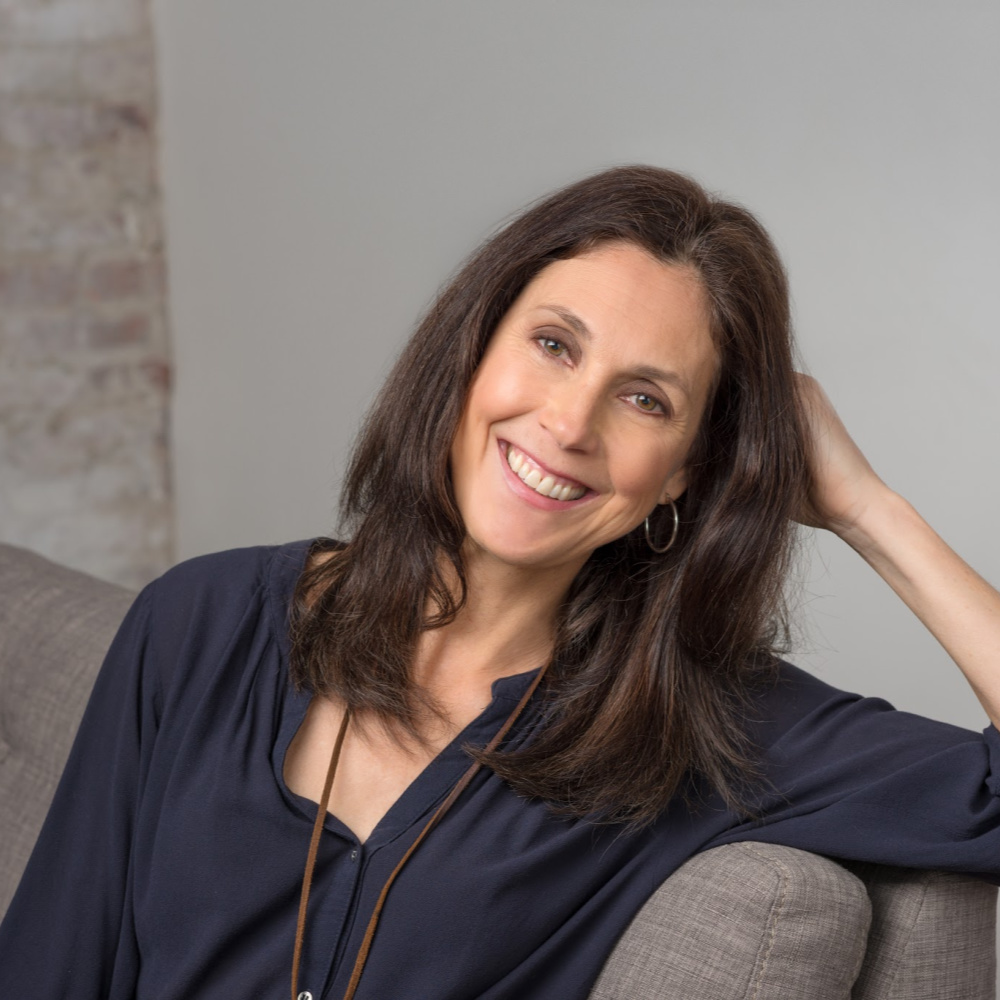 Christina-Petrie-headshot-sitting-grey-couch